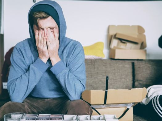 A young person covering his face with his hands