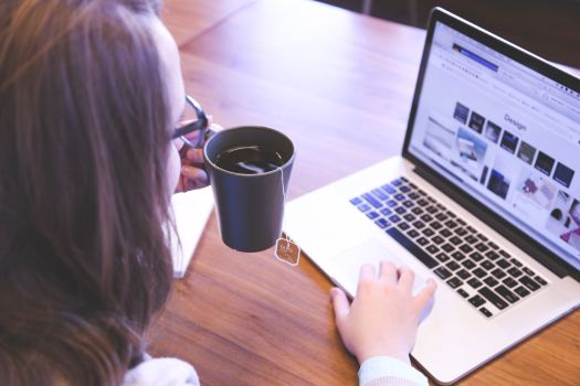 A woman on her laptop with a cup of tea in her hand
