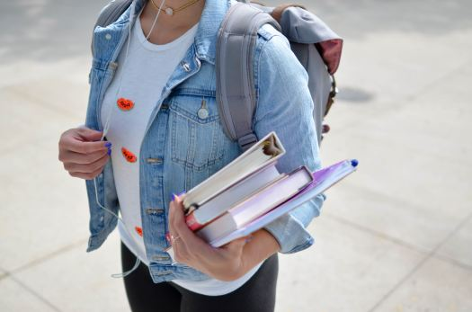 Woman in a denim jacket listening to earbuds and carrying college books